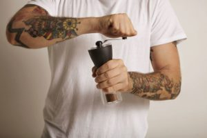 man grinding coffee with manual burr grinder