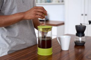 man brewing coffee with a french press