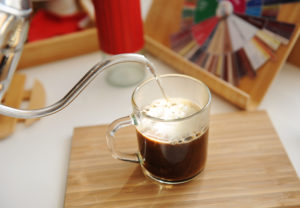 Brewing coffee in mug. Pouring water from gooseneck kettle into a glassy cup with freshly ground coffee.